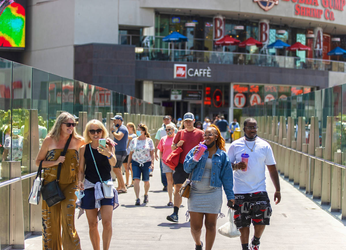 Tourists cross the pedestrian bridge connected to Harmon Corner on the Strip on Friday, April 3 ...