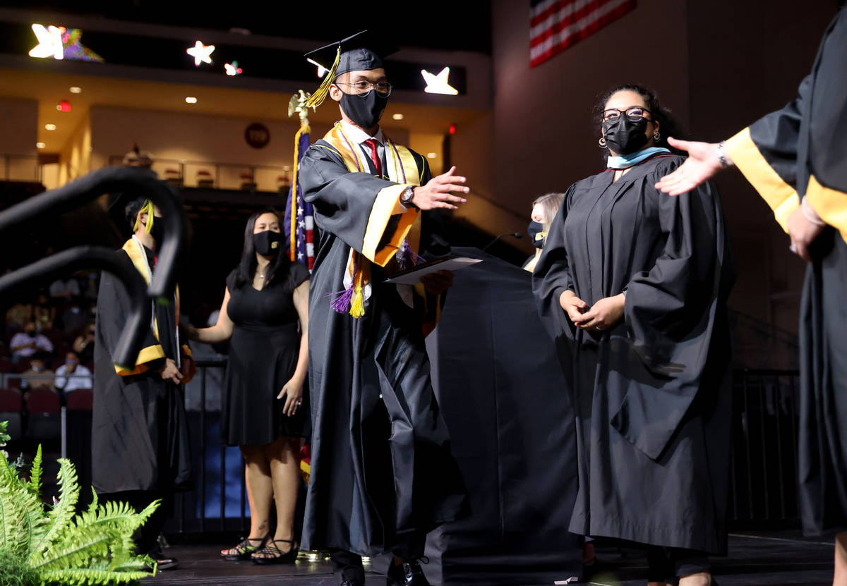 Clark High School student Mark Angelo Yusi walks across the stage after receiving his diploma d ...