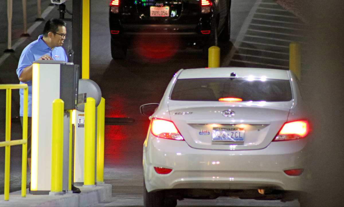 An employee watches a customer pay for parking near the parking garage exit at the Cosmopolitan ...