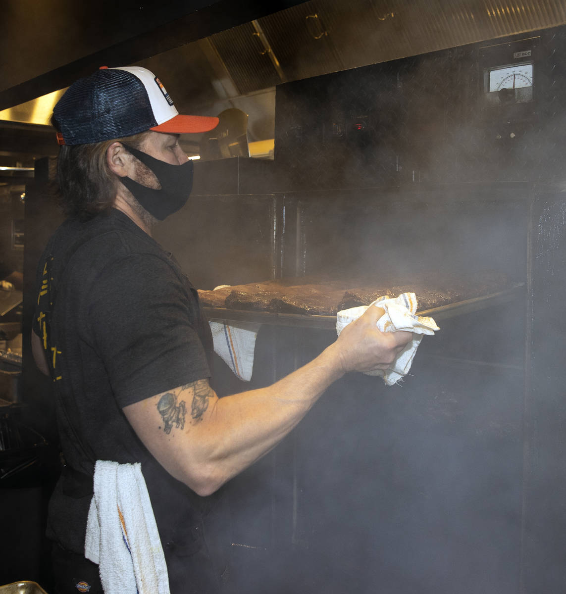 Joe Woodel, BBQ pitmaster, takes racks of smoked pork ribs out of the smoker at The Beast by To ...