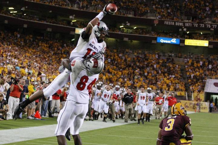 UNLV receiver Phillip Payne, top, celebrates with teammate Rodelin Anthony (84) after Payne bea ...