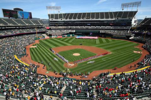 The Los Angeles Angels and Oakland Athletics stand for the national anthem at the Oakland Colis ...