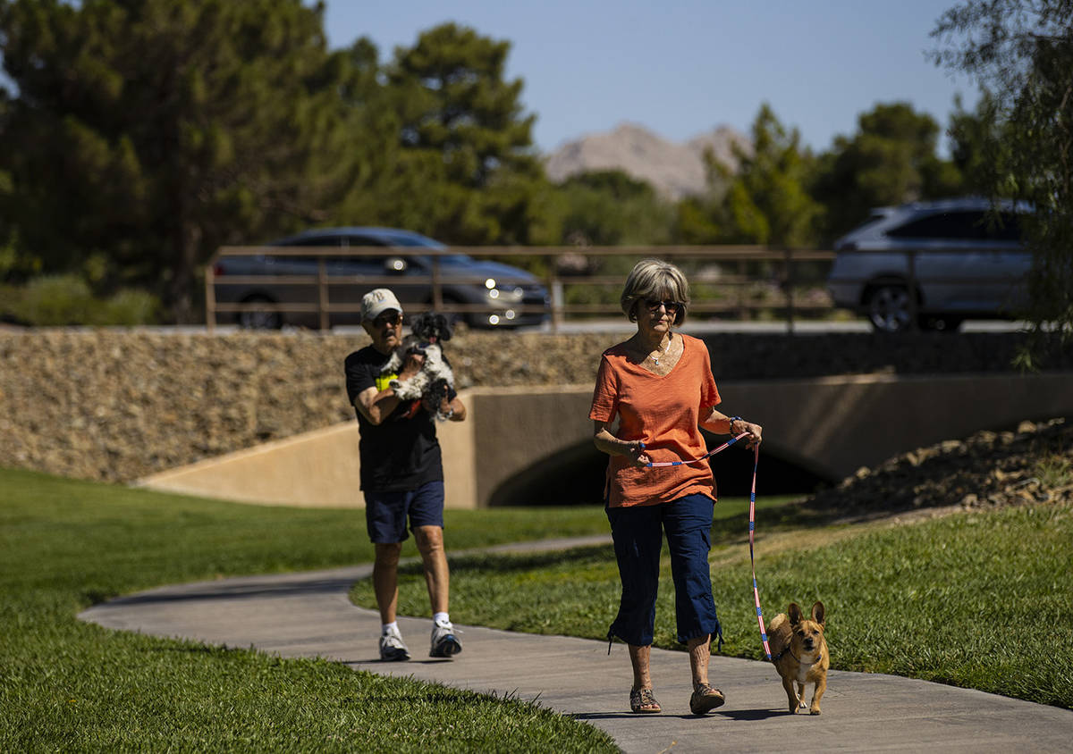 Carol Liberty walks her dog, Mikey, as Phil Sardo, carrying his dog, Mei Mei, walks behind in S ...