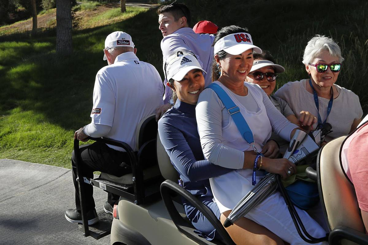 Danielle Kang of USA, center, holds her mother Grace Lee while riding on a cart to the clubhous ...