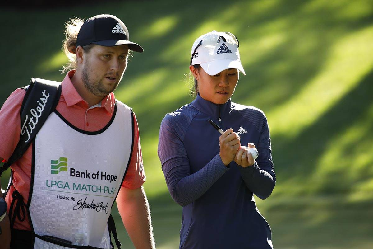 Danielle Kang of USA, signs balls with her caddie after finishing the 15th hole during the thir ...