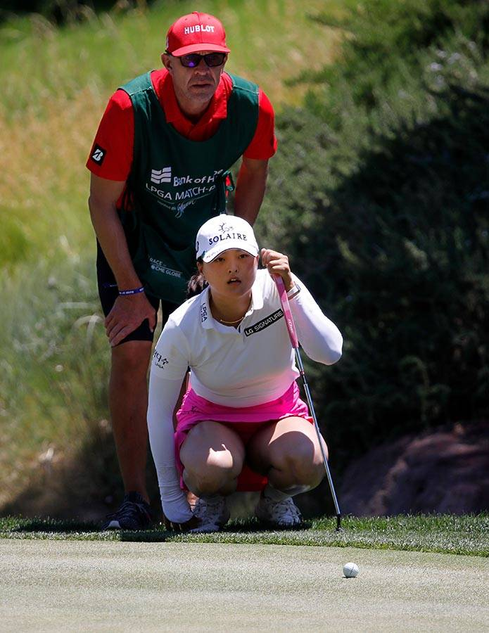 Jin Young Ko of South Korea lines up a putt with her caddie on the first green during the third ...