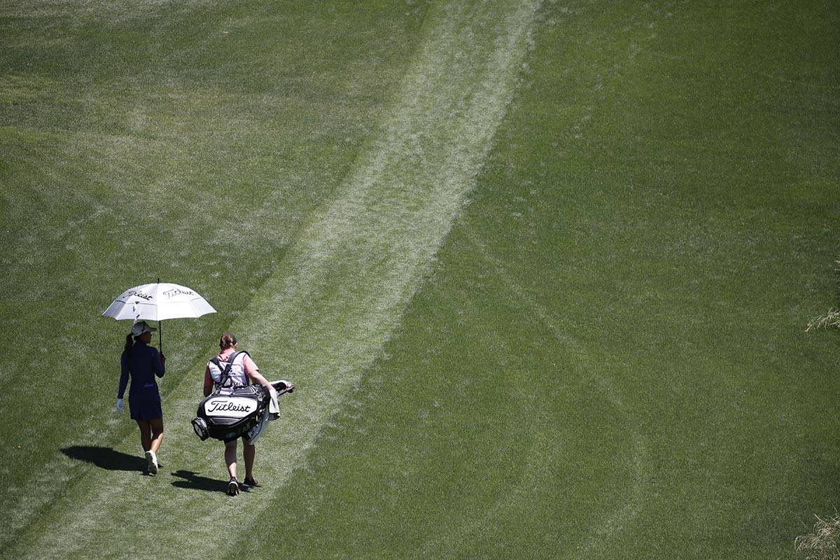 Danielle Kang of USA walks with her caddie after teeing off on the second hole during the third ...