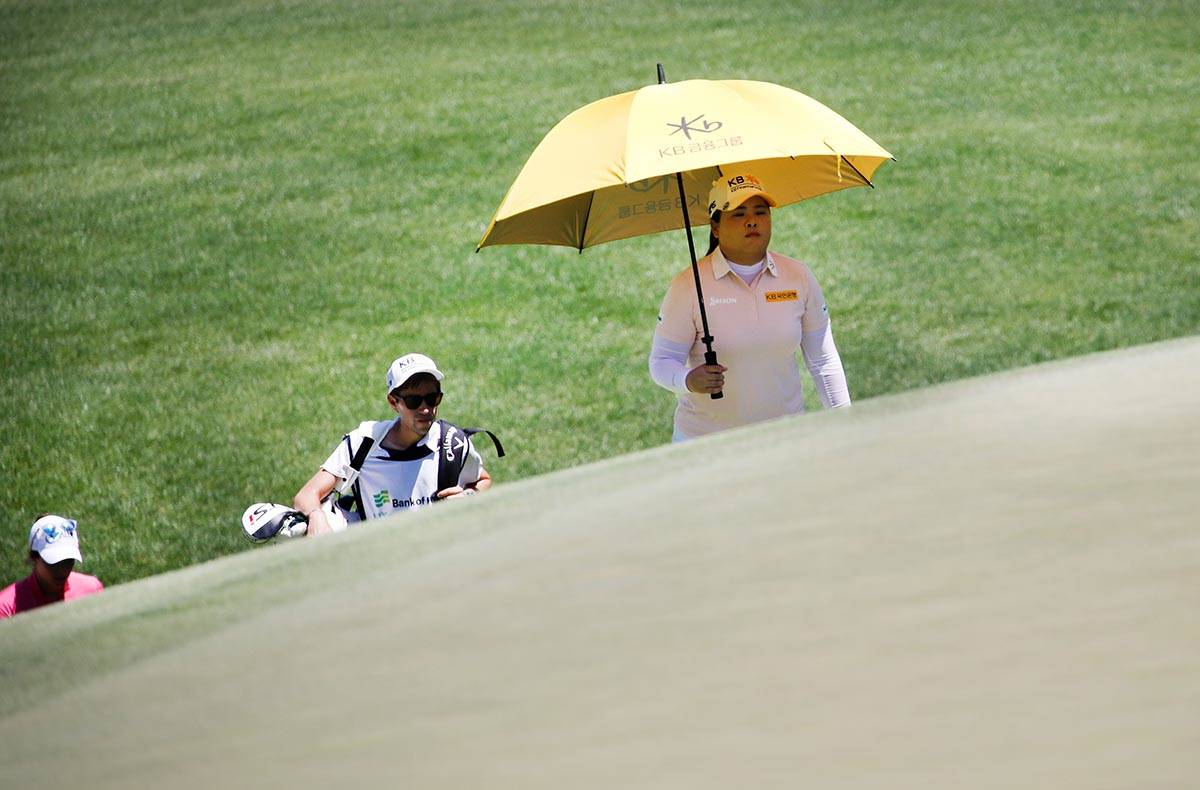 Inbee Park of South Korea, right, walks to the second green with Gaby Lopez of Mexico, left, an ...