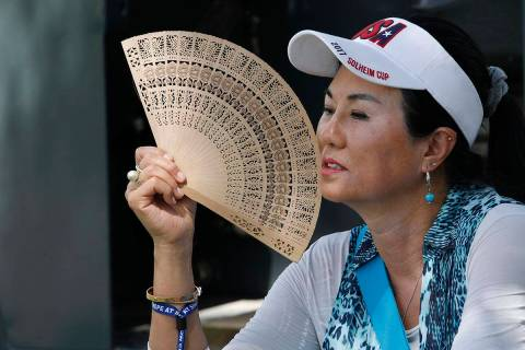 Danielle Kang's mother, Grace Lee, uses a folding fan while waiting on the eighth green to see ...