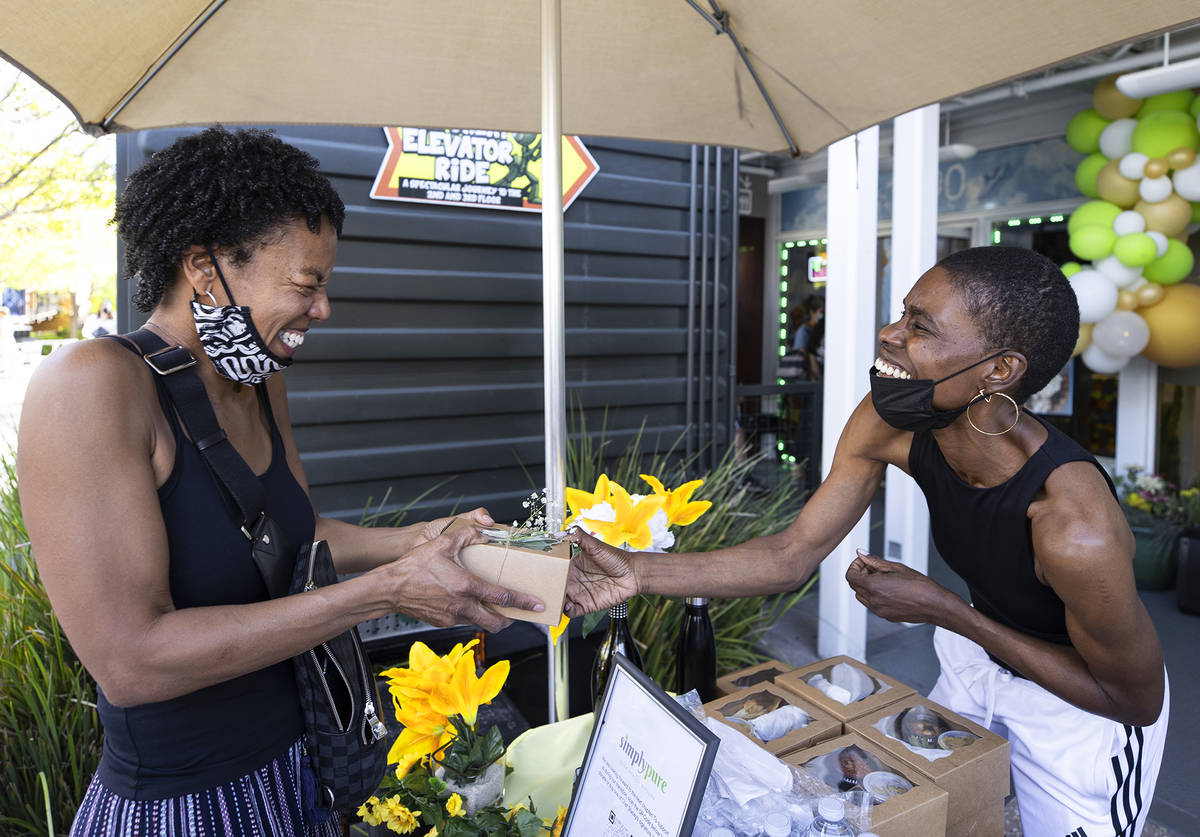 Chef Stacey Dougan gives Roz Brooks a thank-you package at a grand closing celebration for Simp ...