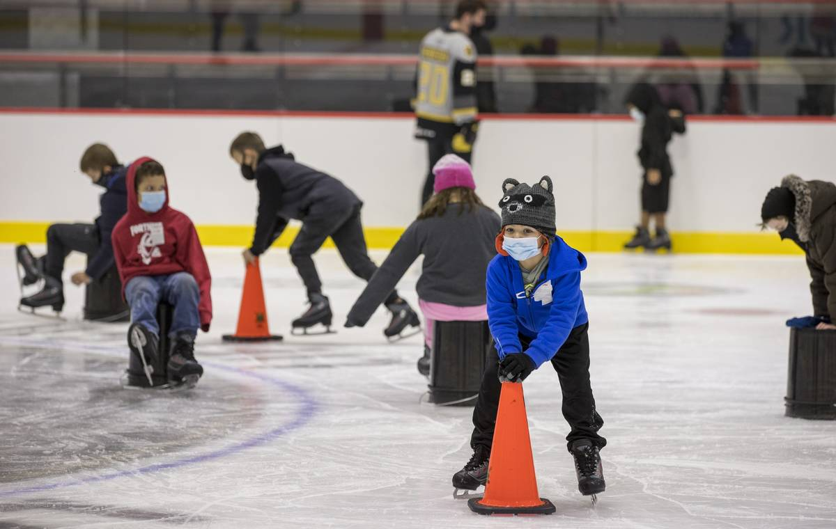 Youngsters with the Battle Born Kids Program use cones and buckets to stay upright on the ice d ...