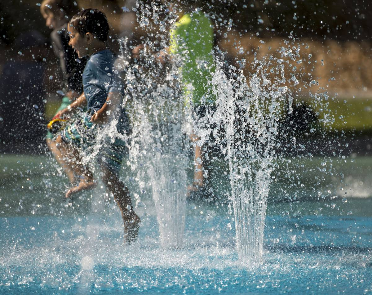 Leo Reyes, 3, runs through the water fountains as he stays cool on the splash pad at The Paseos ...