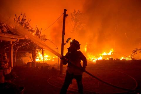 A firefighter works against the Lake Hughes Fire in Angeles National Forest north of Santa Clar ...