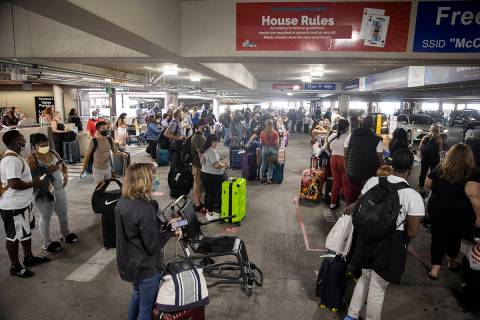 People wait for their ride at McCarran International Airport's Terminal 1 ride share waiting ar ...