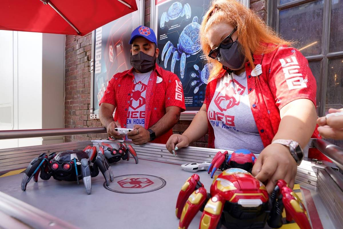 Cast Members Ryan Garcia, left, and Cristal Aros demonstrate Spider-Bots toys at the Avengers C ...