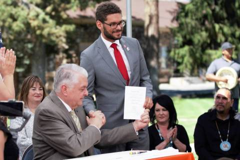 Gov. Steve Sisolak, left, shakes hands with Assemblyman Howard Watts, D-Las Vegas, after signin ...