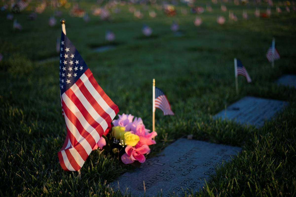 The sun sets on a Korean War veteran's grave on Memorial Day at the Southern Nevada Veterans Me ...