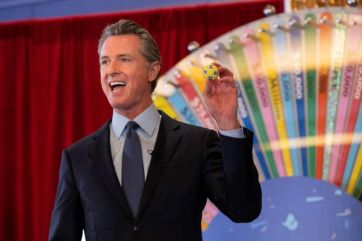 California Gov. Gavin Newsom holds up a lottery ball at the California Lottery Headquarters on ...