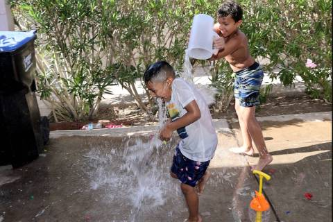 Dominic Perry, 7, soaks Zair Perez, 6, while cooling off at their grandfather's house in the Be ...