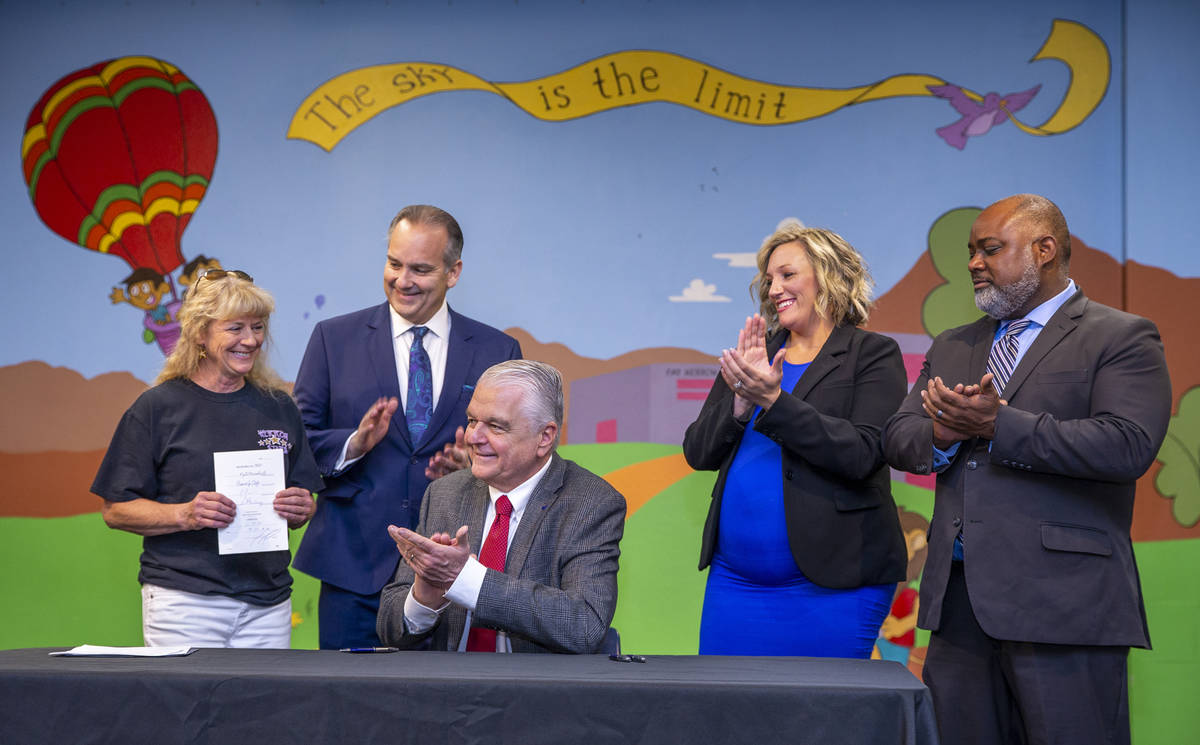(From left) Principal Judy Jardahl holds Senate Bill #450 while applauded by Clark County Schoo ...