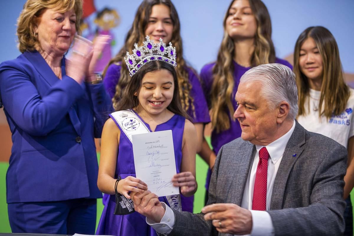 Gov. Steve Sisolak hands Miss Nevada Role Model Tayla Westerman his signed Senate Bill #249 dur ...