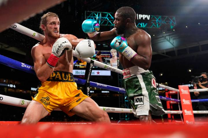 Floyd Mayweather, right, throws a punch at Logan Paul, left, during an exhibition boxing match ...