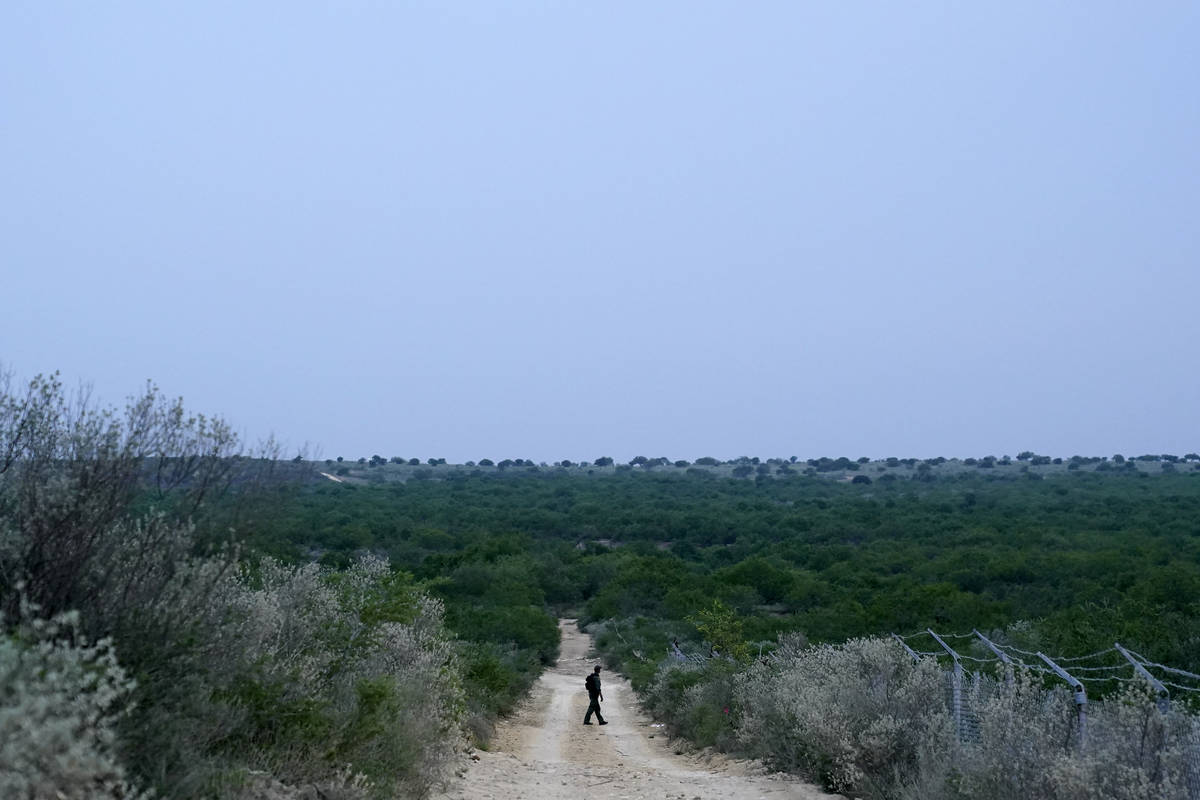 FILE - In this May 11, 2021, file photo a Border Patrol agent walks along a dirt road near the ...