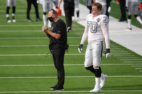 Las Vegas Raiders offensive line coach Tom Cable, left, claps after the team scores a field goa ...