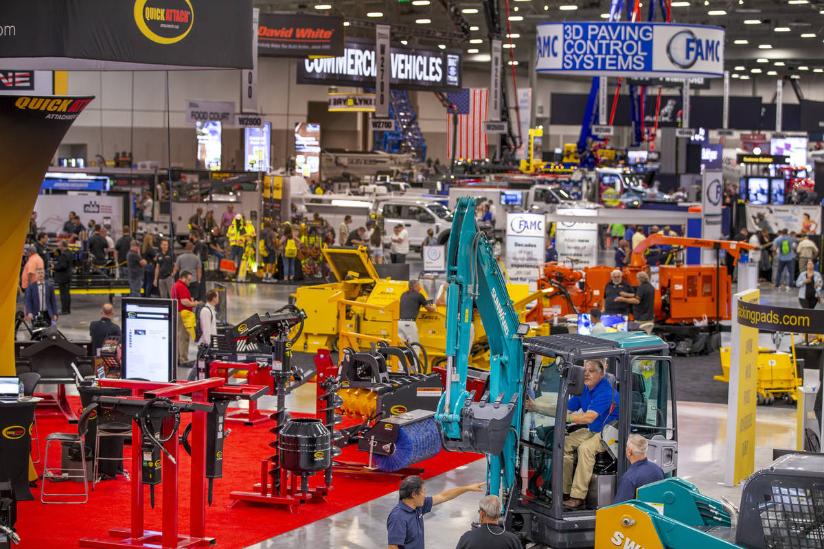 World of Concrete 2021 attendees check out a Sunward excavator at a display about the trade-sho ...
