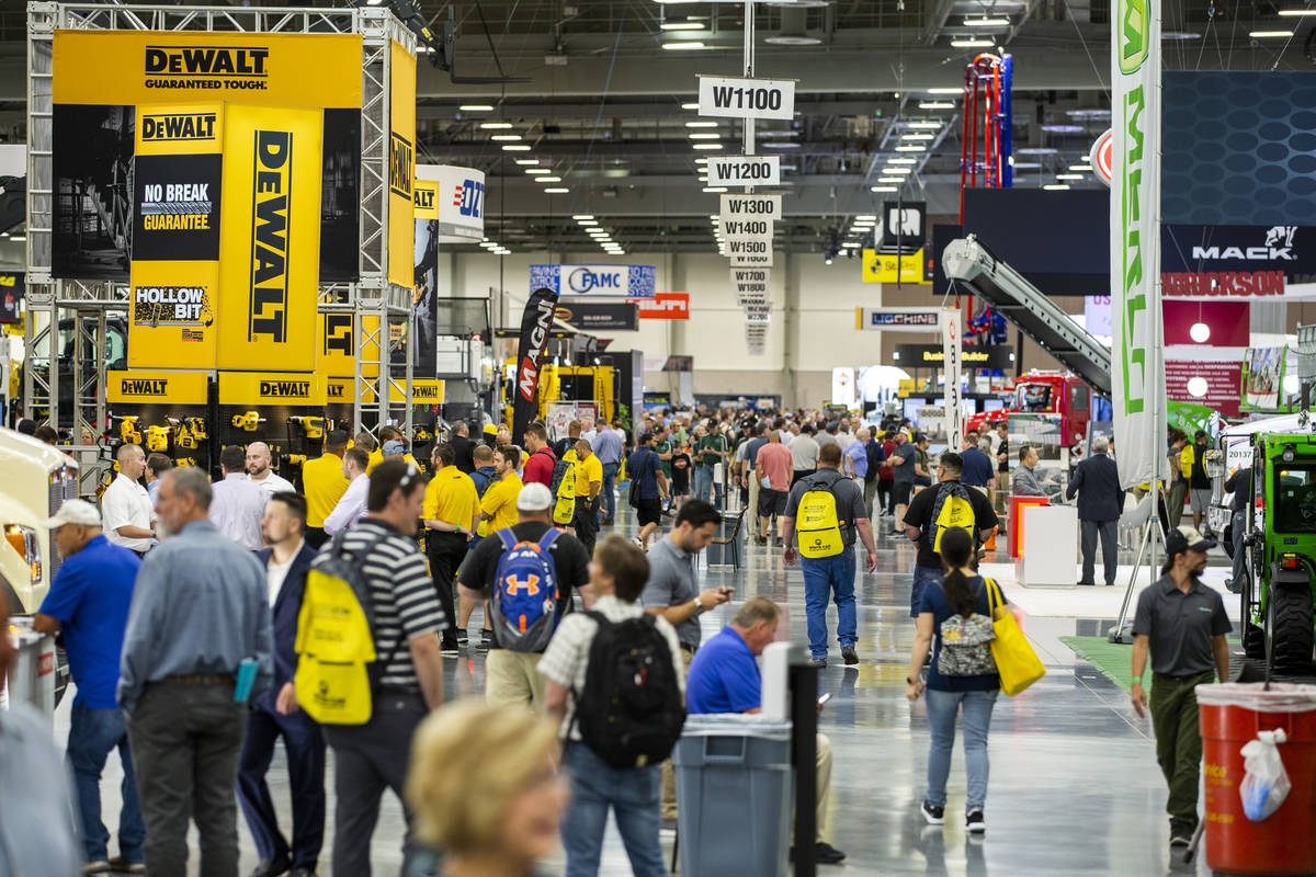 World of Concrete 2021 attendees wander about the displays on the trade-show floor in the West ...