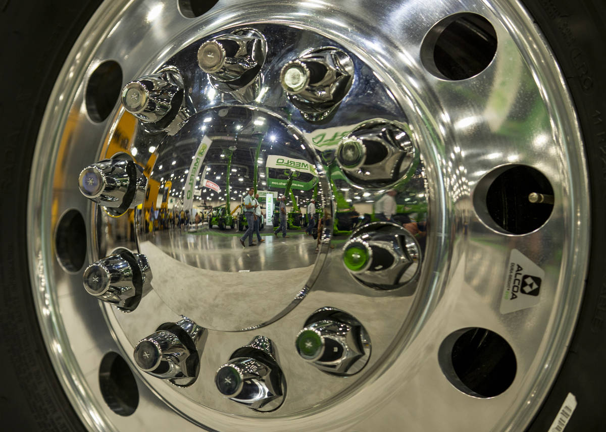 World of Concrete 2021 attendees are reflected in the rim of a Peterbilt truck on display about ...