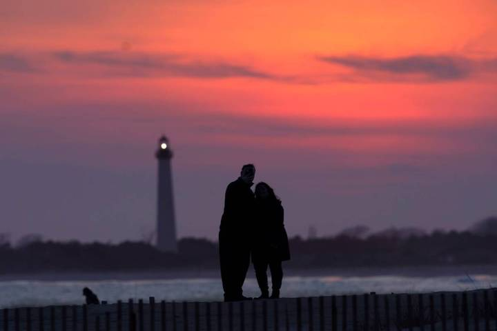 Visitors to Cape May, N.J., watch the sunset behind the Cape May Lighthouse on April 8, 2021.(A ...