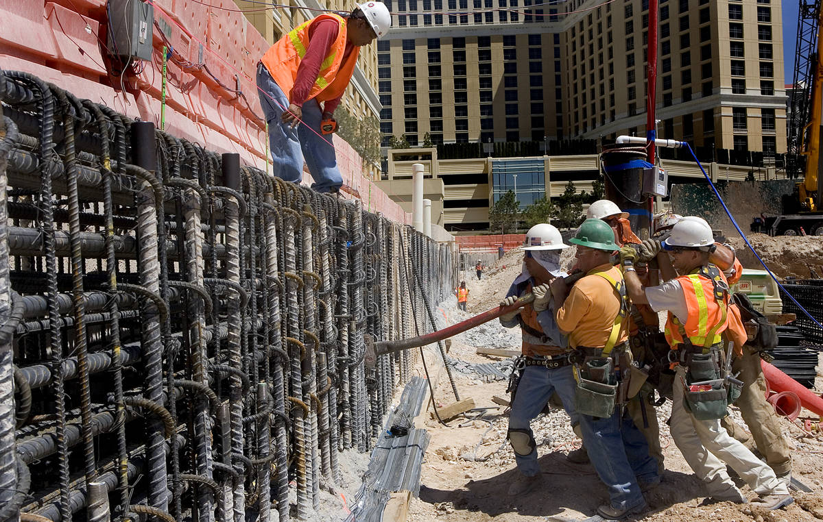 Perini Building Co. construction workers use a hickeybar to straighten a piece of rebar in the ...