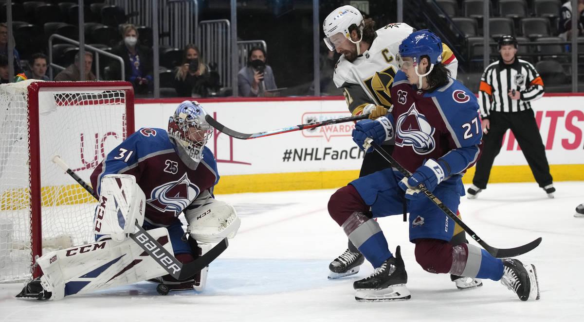 Colorado Avalanche goaltender Philipp Grubauer, left, stops a shot as defenseman Ryan Graves, f ...