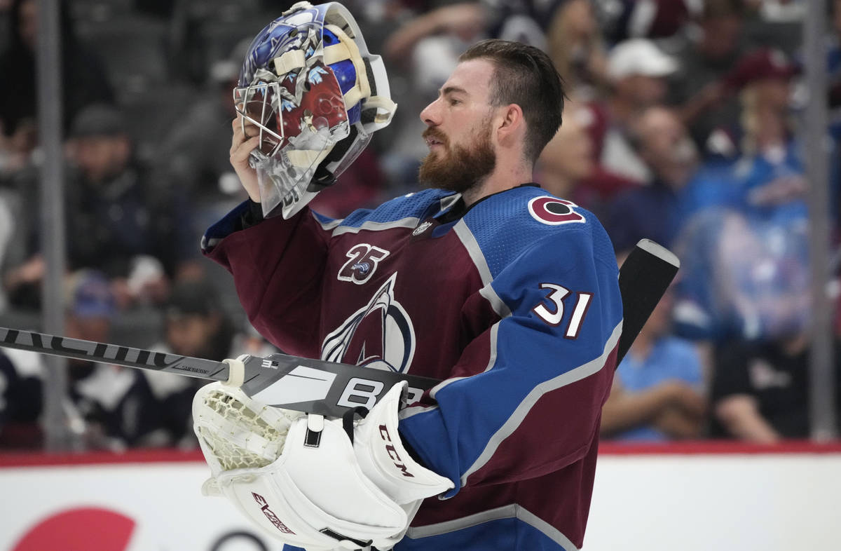Colorado Avalanche goaltender Philipp Grubauer puts on his mask during a timeout in the first p ...