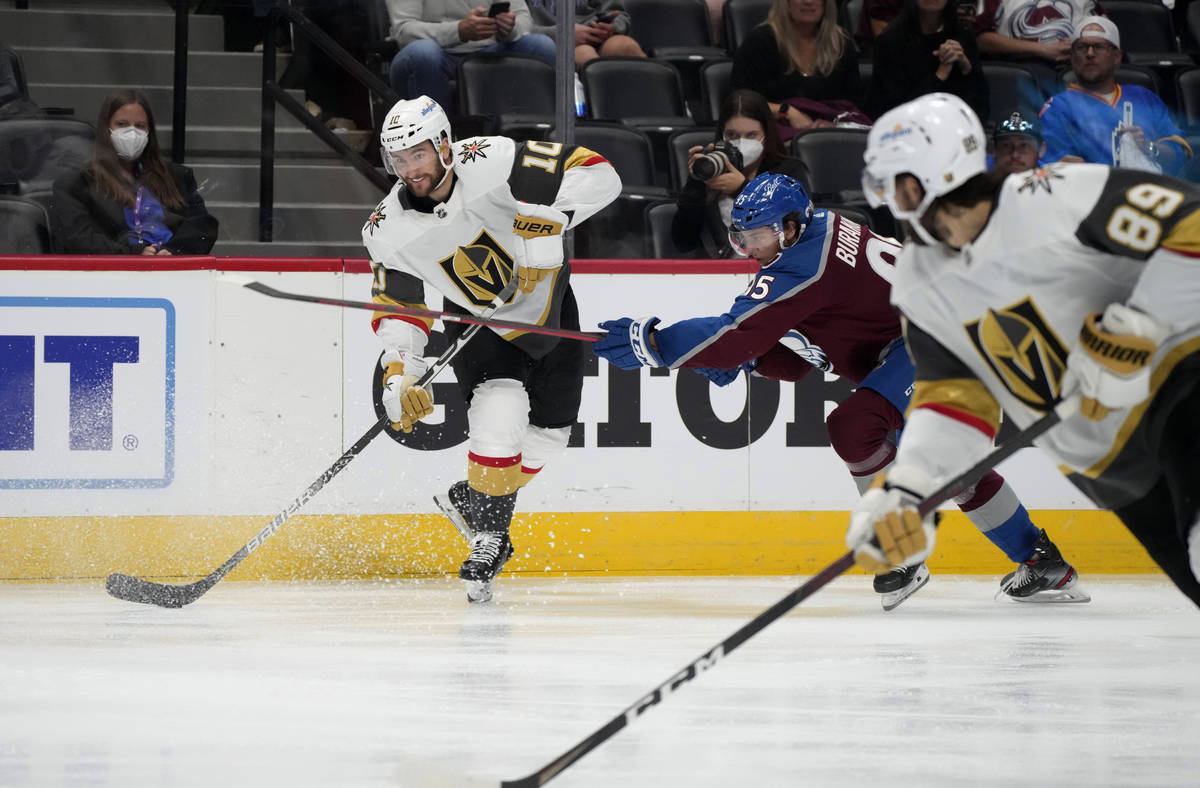 Vegas Golden Knights center Nicolas Roy, left, lifts a pass to right wing Alex Tuch, front, as ...