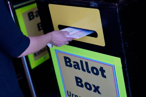 In this Oct. 29, 2020, file photo, a person places a mail-in ballot in a drop box at the Clark ...