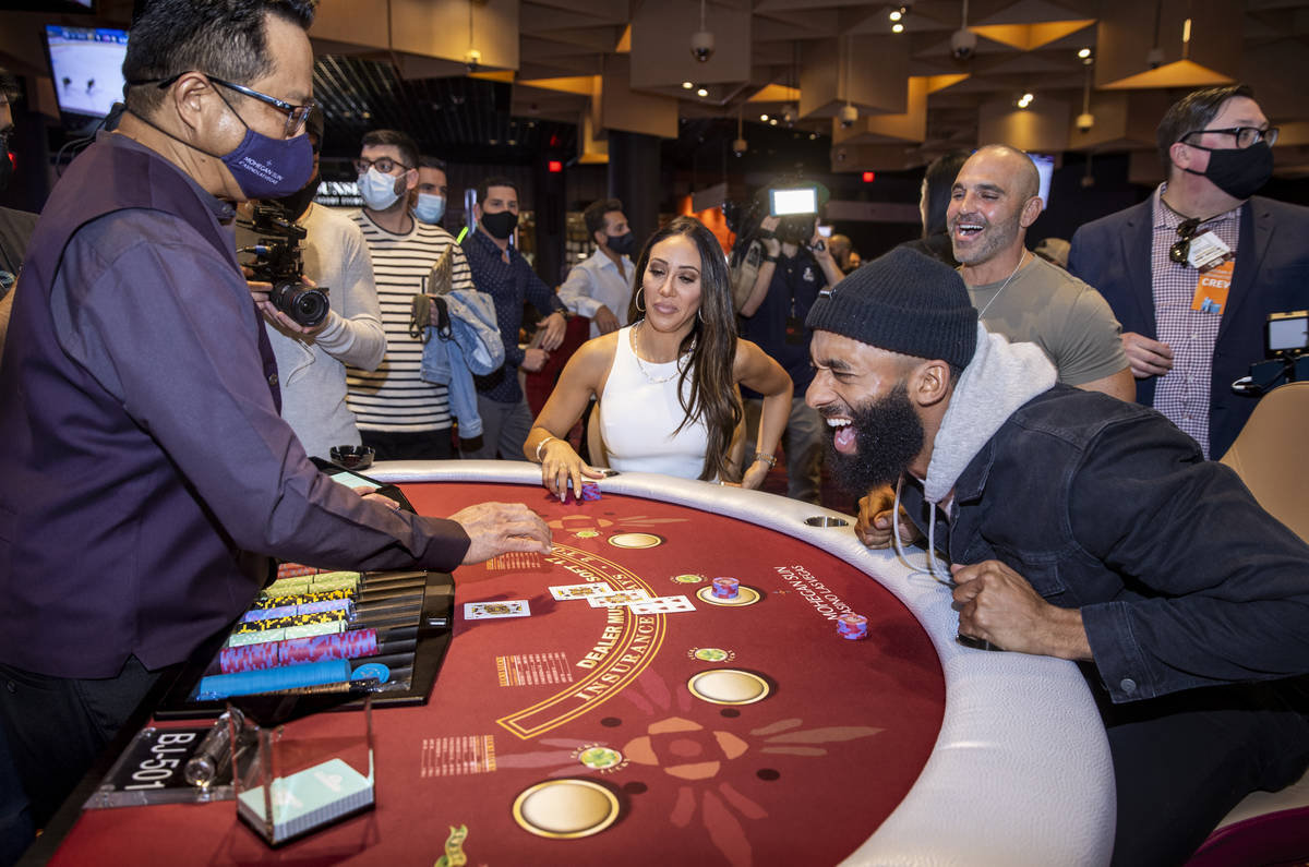 Matt James, right, with Melissa George, center, reacts to the final card being laid down as he ...