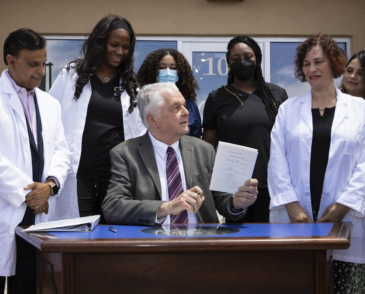 Gov. Steve Sisolak holds Senate Bill # 420, the bill that will provide a public health care opt ...
