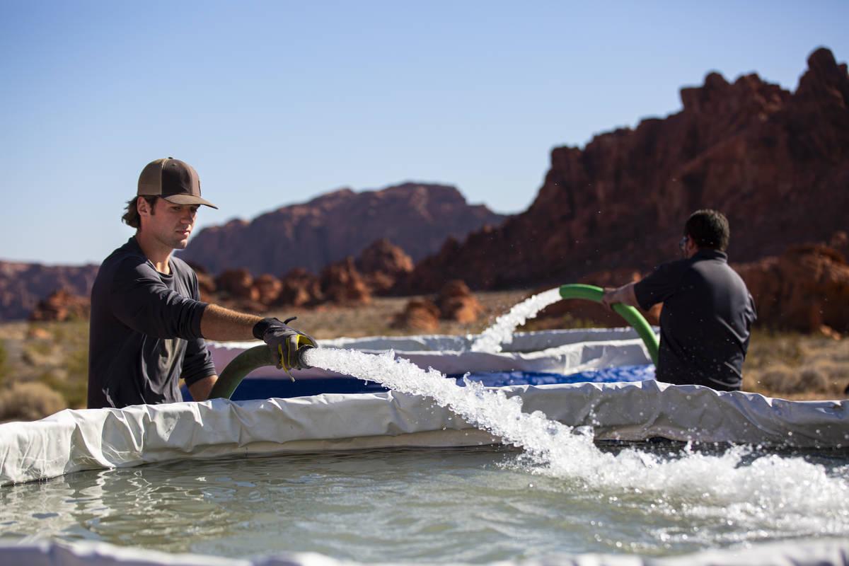 Seth Wilson, a Lathrop-Capurro memorial intern with the Nevada Department of Wildlife, replenis ...