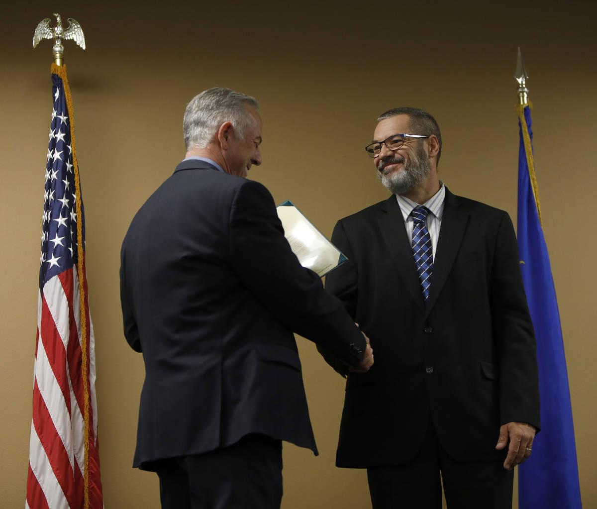 Clark County Sheriff Joe Lombardo, left, shakes hands with Scott Miller, retired detective, who ...
