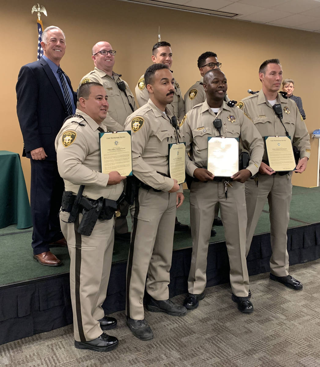 Clark County Sheriff Joe Lombardo, background left, poses for a photo with the recipients of un ...