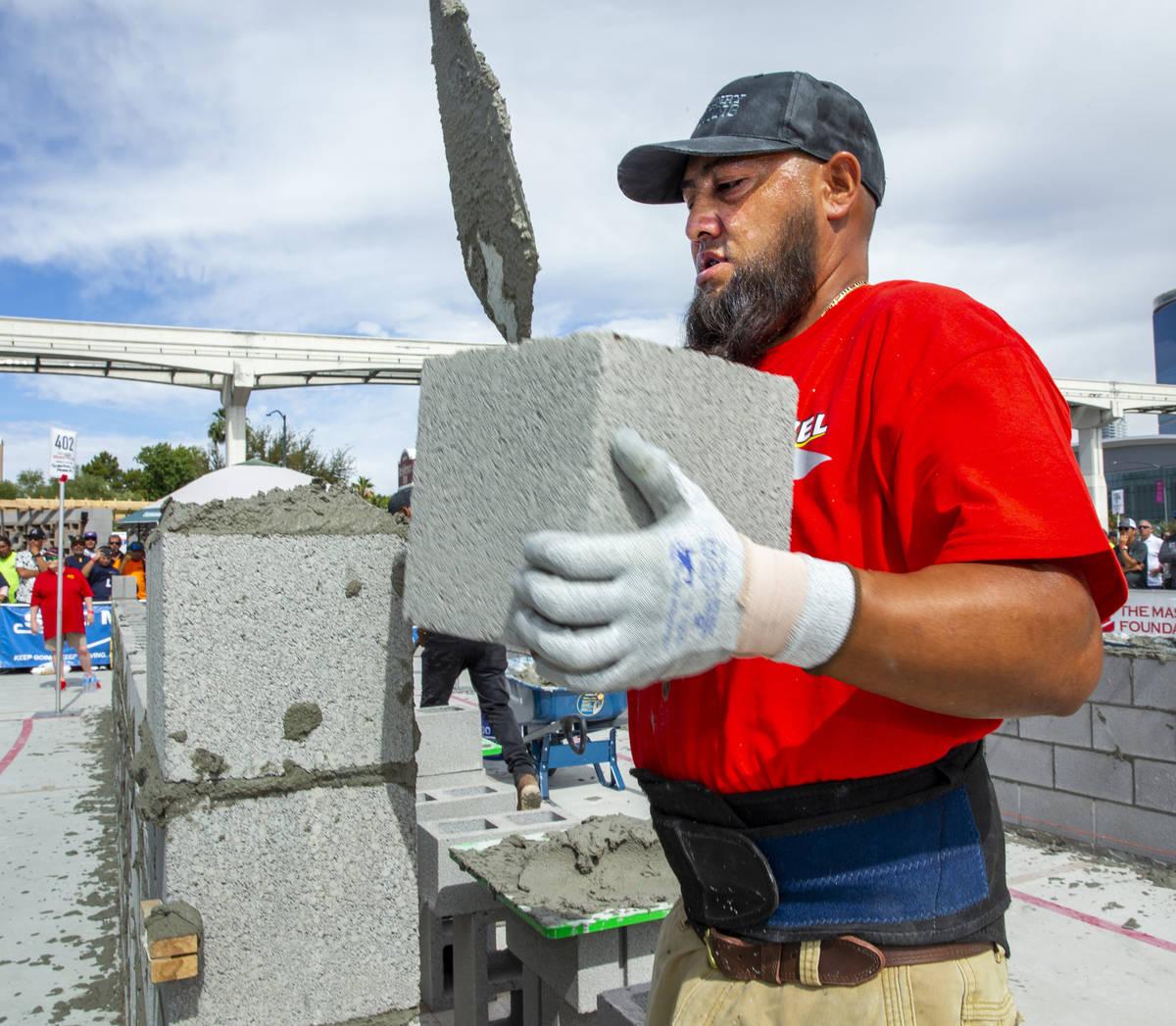 Gerardo Patlan of Phoenix, Arizona, stacks a concrete block in the Fastest Trowel on the Block ...