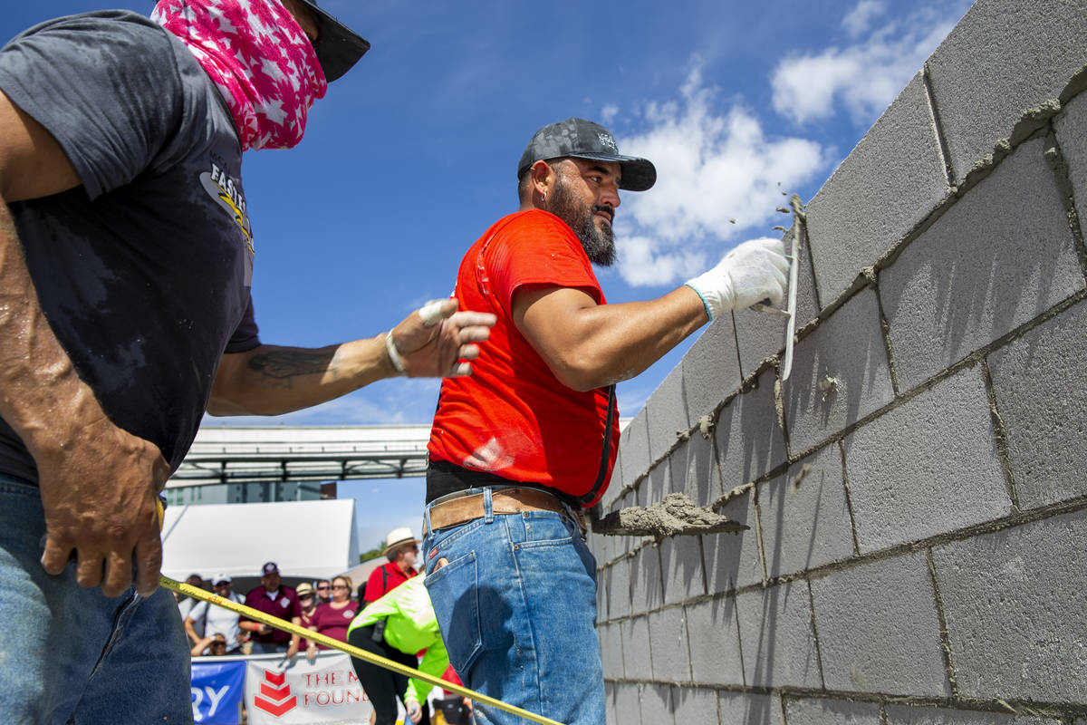 Jose Soto, right, and tender Israel Mendoza clean up concrete block in the Fastest Trowel on th ...
