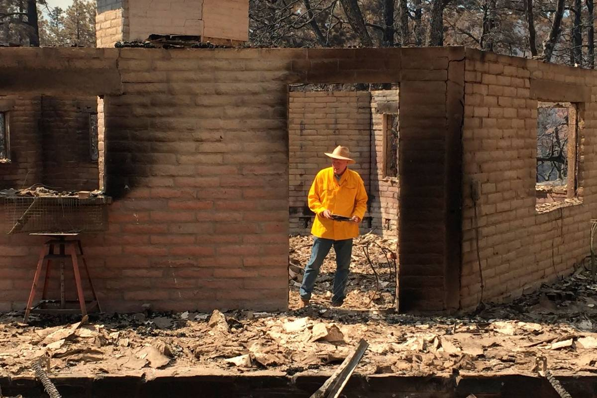 Arizona House Speaker Rusty Bowers walks through the remains of his family's weekend home on Tu ...