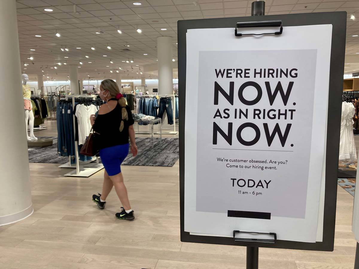 A customer walks behind a sign at a Nordstrom store seeking employees, Friday, May 21, 2021, in ...