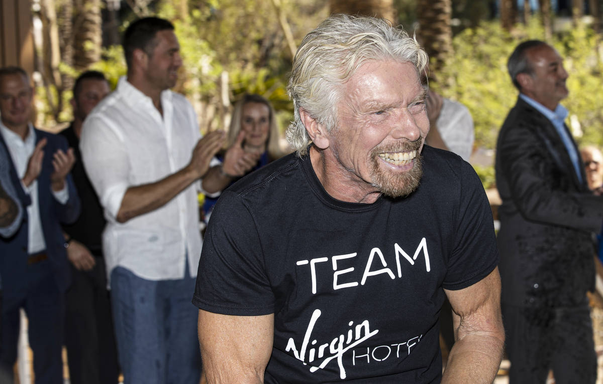 Sir Richard Branson, right, founder of Virgin Group, shares a laugh with attendees after poppin ...