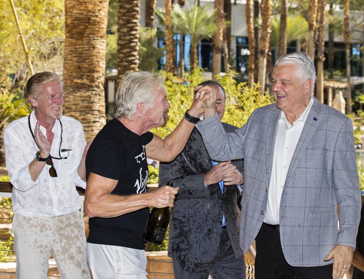 Sir Richard Branson, second from left, founder of Virgin Group, high fives Gov. Steve Sisolak a ...