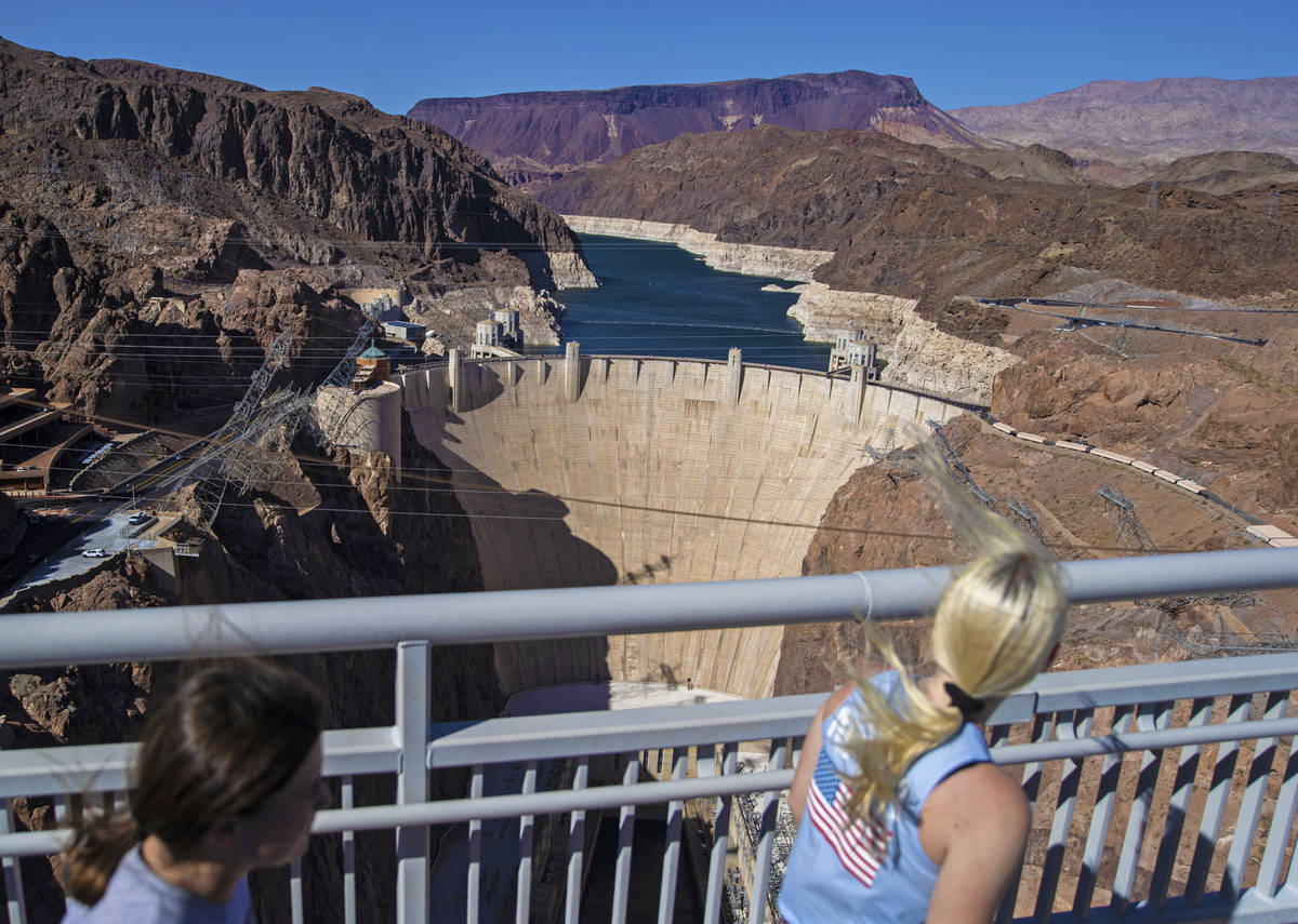 Tourists look out at Lake Mead and the Hoover Dam while walking on the Mike O'CallaghanÐPa ...