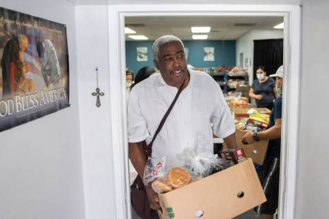 Jimmy Stewart walks out of the food bank with a box of groceries at City Impact Center on Tuesd ...